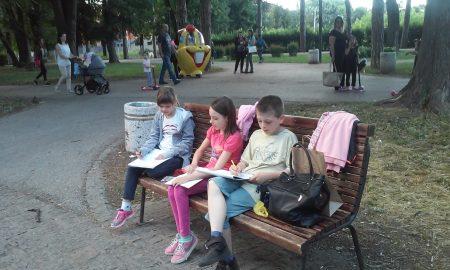 Deca koja sede na klupici u parku