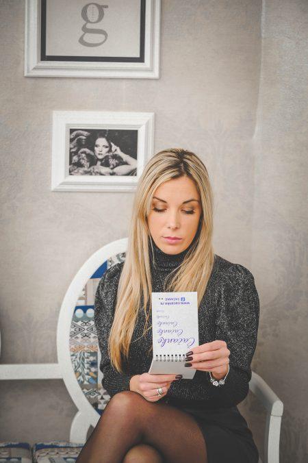 Devojka koja sedi na stoliocio i čita nešto iz sveske.